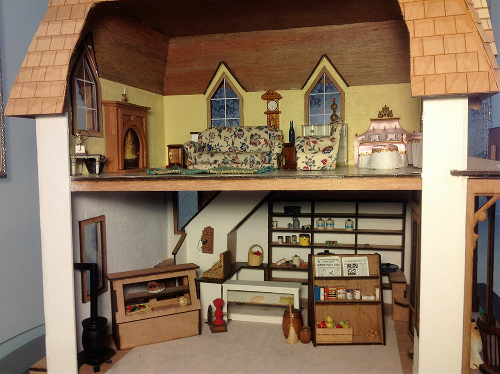 Photo of a dollhouse interior with a livingroom upstairs and a hobbyroom/basement downstairs