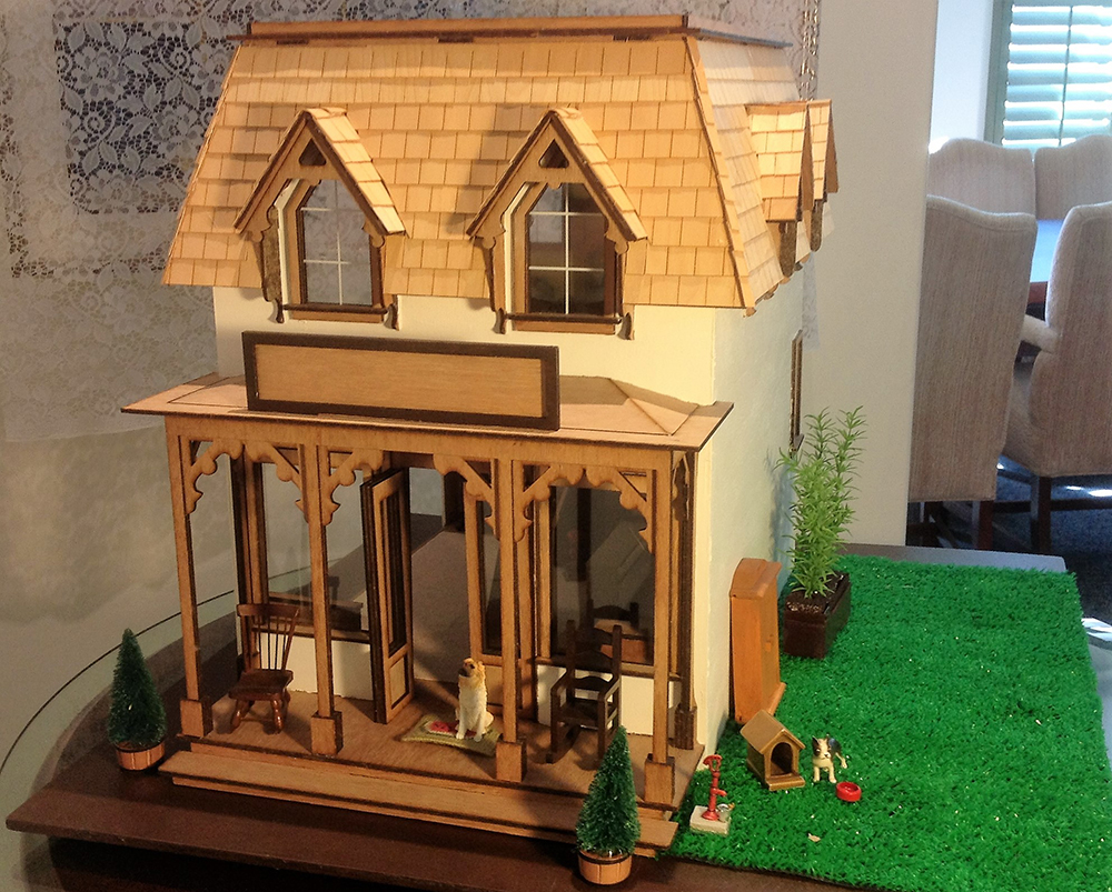 Exterior view of dollhouse, with dog sitting by front door and a smaller pooch by doghouse to the right
